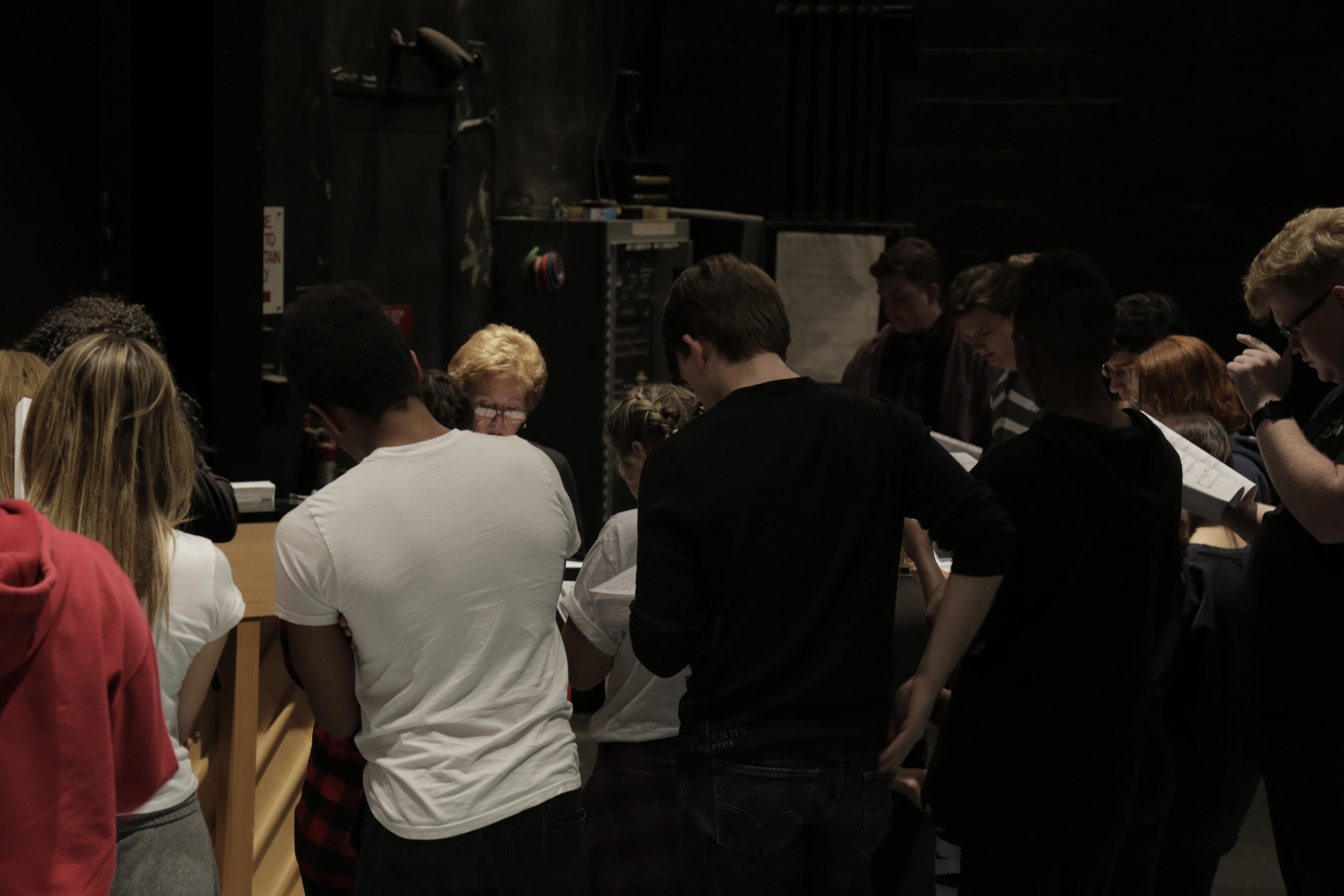 Students huddled around musical director Marilyn Anderson