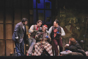 Rodolfo (Mario Chang) and his friends charmingly avoid having to pay their landlord (Philip Cokorinos, center). Photo Credit: Robert Millard, LA Opera